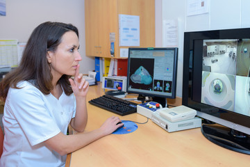 Medical worker looking at imagery on screen