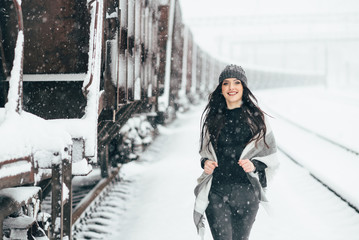 Young pretty girl against the backdrop of a railroad road.