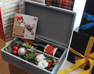Gray box with a gift. A bottle of red wine, spruce branches, Christmas balls