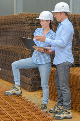 Man and woman stood by stack of rebars