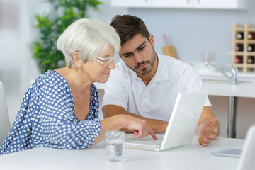 Young man helping senior lady to use a laptop