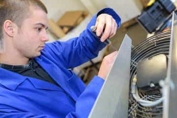 a young man repairing a fan