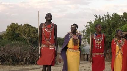 Wall Mural - panning shot of a group of maasai women and men singing and dancing at a village near masai mara,kenya
