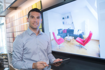 Man stood by screen showing image of a lounge area