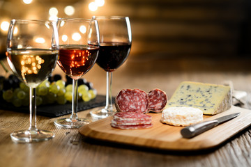 three glass of red wine, rose wine and white wine with french cheese and delicatessen in restaurant wooden table with romantic dim light and cosy atmosphere