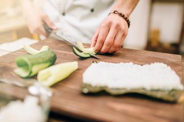 Male cook hands closeup, making sushi rolls