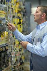 male customer buying working tools in supermarket
