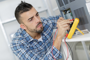 engineer using a voltage and current tester