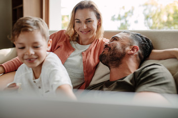 Happy young family relaxing on couch at home