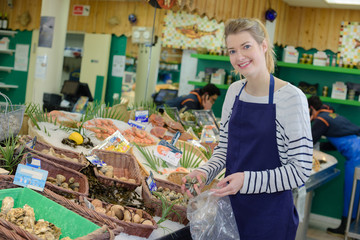 smiling woman in apron selling organic fruits in shop
