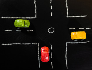 Red Green and Yellow wooden car toys stop on crossroad of chalk board