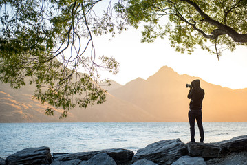 Young male photographer taking photo under the tree at Lake Wakatipu during golden hour sunset in Queenstown, South island, New Zealand, travel and landscape photography concepts