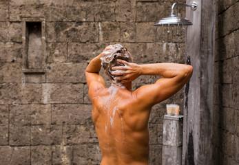 Man washing hair in outdoor shower