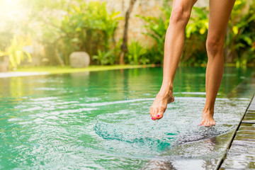 Woman splashing pool water with her leg