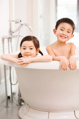 The lovely boy and girl are in the bathtub