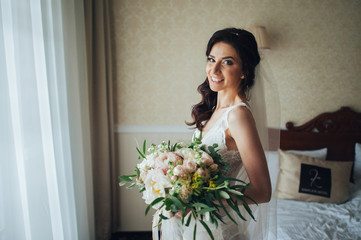 beautiful bride with a bouquet of flowers in the hotel room