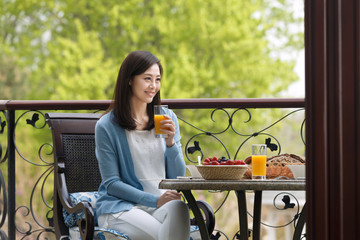 A middle-aged woman eats breakfast on the terrace