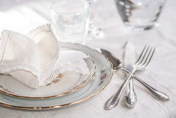 Luxury dinner set with silverware, elegant porcelain dishes, crystal glassware and vintage lace napkins