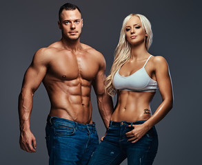 Attractive fitness couple over grey background.
