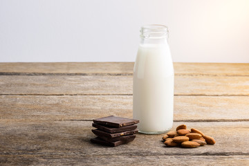milk in bottle, chocolate and almond on wooden