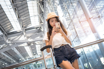 Asian woman teenager using smartphone at airport terminal with luggage suitcase and backpack for travel in vacation summer relaxing waiting flight transport online check in or booking ticket