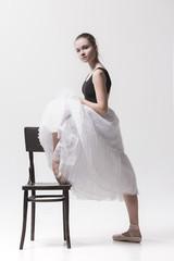 The teen ballerina in white pack posing near chair