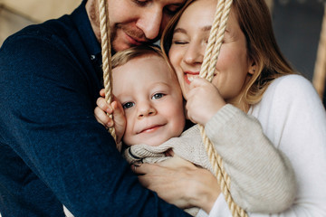 Mom and dad play with charming little son on a swing in the room