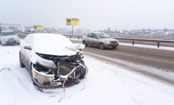 An accident with a white car in winter on road, slippery icy road, danger driving