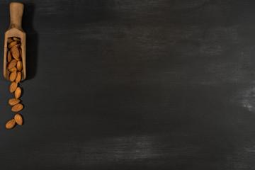 Almonds in a wooden scoop in a black chalkboard.