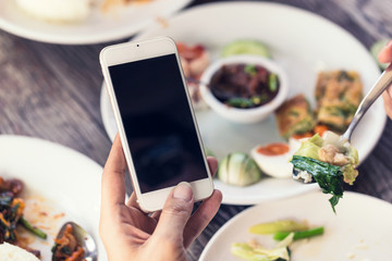 close up of woman hand using or looking at her smartphone and having lunch in the restaurant.