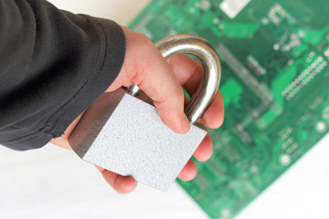 access is closed/ large padlock holds a hand in a black sweater on a computer circuit background