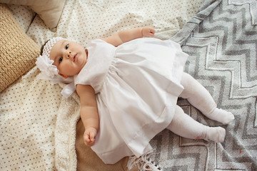 beautiful, little girl in a white dress. little six months old baby in studio on bed