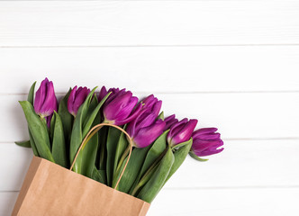 Tulips in  paper bag on the white table