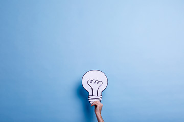 The hand of a man holds a image of a light bulb. Blue background. Concept of the idea.