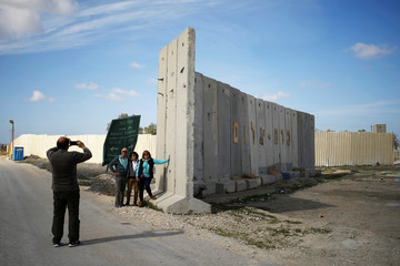 Tourists pose for a photo near the entrance to the Kerem Shalom border crossing terminal to the southern Gaza Strip