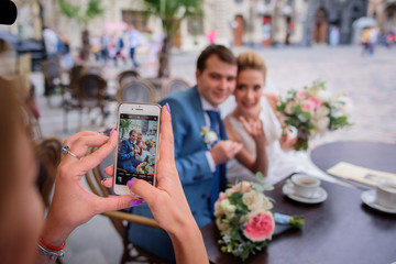 Woman takes a picture of stunning newlyweds sitting in the cafe