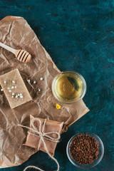 top view of natural soap, oil and coffee scrub for spa on crumpled paper on green marble surface