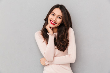 Image of gorgeous brunette female model with long hair and red lips posing on camera with brilliant smile over gray wall
