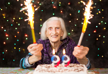 Happy grandma celebrating 99th birthday with firework