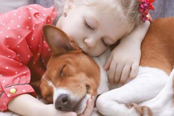 Little blonde curly girl hugging a red basenji dog.