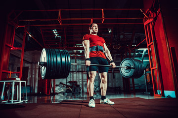 Muscular fitness man doing deadlift a barbell in modern fitness center. Functional training. Snatch exercise. Sumo style.