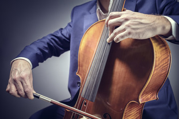 Cello player or cellist performing