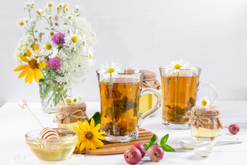 A healthy Cup of  herbal tea, a jar of honey and wild flowers. On white background