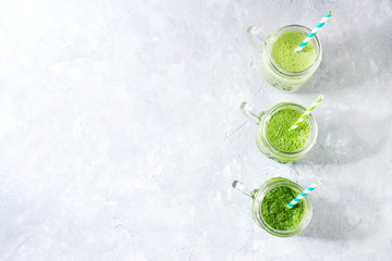Variety of three color green spinach kale apple yogurt smoothie in mason jars in row with retro cocktail tubes over gray background. Healthy vegan detox eating. Top view, copy space