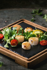Fried scallops with lemon, cherry tomatoes and green salad served on wooden black slate serving board over old dark metal background. Close up