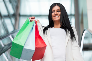 Beautiful woman leaving the mall with plenty of shopping bags