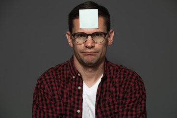 Portrait of depressed man in glasses and casual clothes with  blue sheet on his forehead on gray background. Copyspace