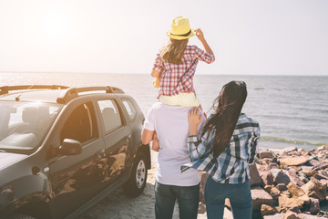 Happy family standing near a car on the beach. Happy family on a road trip in their car. Dad, mom...