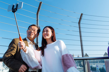 Japanese grandfather and granddaughter taking selfies and photos from the top of Arena mall Barcelona enjoining the views of Plaza de España, Montjuic and palau nacional.