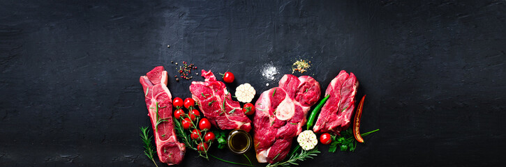 Foto auf Acrylglas Fleisch Raw fresh meat steak with cherry tomatoes, hot pepper, garlic, oil and herbs on dark stone, concrete background. Banner.